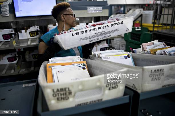 A worker carries a mail tray next to an advanced face cancelling machine at the United States Postal Service Suburban processing and distribution...