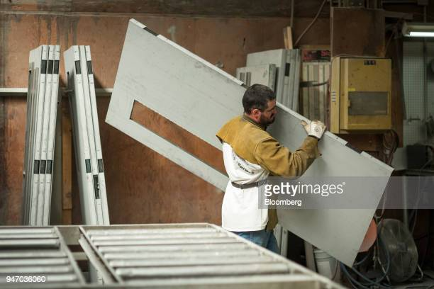 A worker carries a metal door during production at the Metal Manufacturing Co facility in Sacramento California US on Thursday April 12 2018 The...