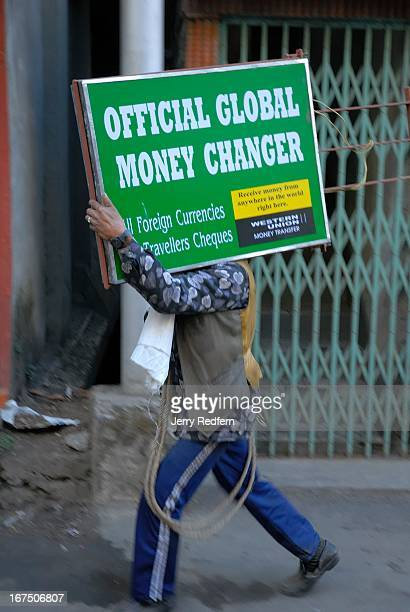 A worker carries a new business sign down the streets of Darjeeling The old Britishera hill station is still a destination for tourists from around...