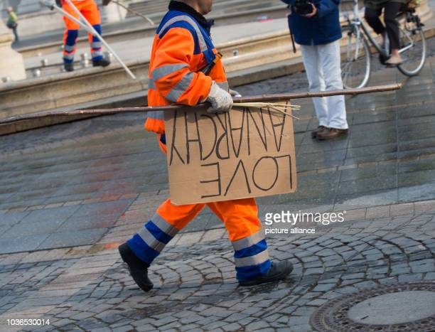A worker carries a protest sign written with 'Love Anarchy' to the trash one day after the demonstrations against the official opening of the new...