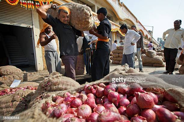 A worker carries a purchased bag of onions at a wholesale market in Nashik Maharashtra India on Wednesday Oct 23 2013 Onion prices in India may...