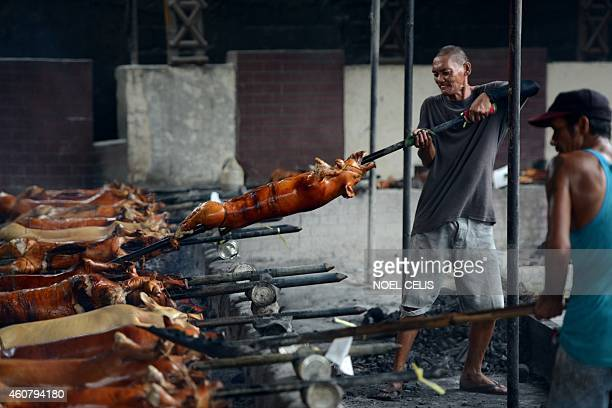 A worker carries a roasted pig to be displayed along a street in Manila on December 23 for the busy holiday season Lechon or roasted pig has always...