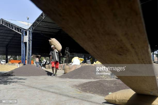 A worker carries a sack of barley to a truck at a wholesale grain market in Rewari Haryana India on Wednesday March 28 2018 India's Prime...