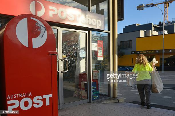 A worker carries a sack of letters after emptying a post box outside an Australia Post office in Sydney on June 26 2015 Australia Post was June 26...