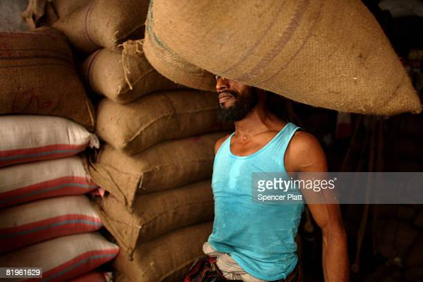 A worker carries a sack of rice on his head after it is transported to market on July 17 2008 in Dhaka Bangladesh Bangladesh has recently closed...