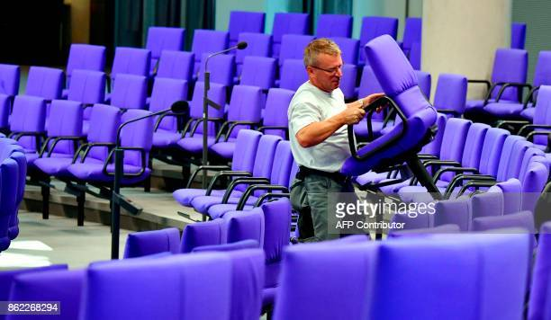 A worker carries a seat in the plenary at the German lower house of parliament the Bundestag in Berlin on October 17 2017 For the first session of...