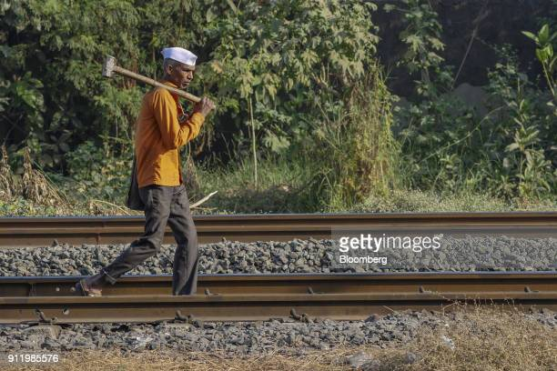A worker carries a sledgehammer as he walks along rail tracks in Mumbai India on Saturday Jan 27 2018 Mumbai's suburban railway the oldest in Asia is...