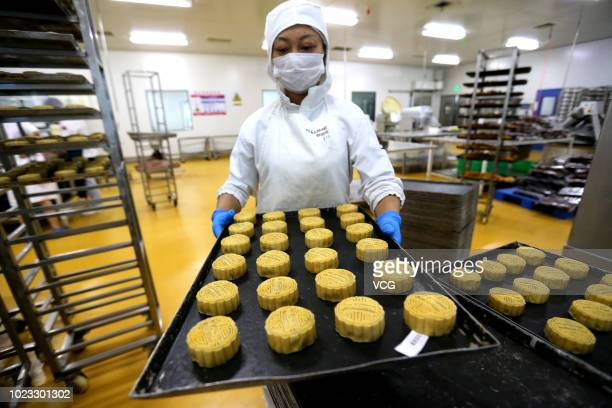 A worker carries a tray of mooncakes at a mooncake factory on August 21 2018 in Meishan Sichuan Province of China Mooncake is the traditional food...