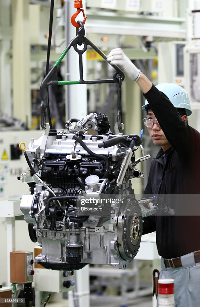 A worker carries an engine for the Toyota Motor Corp. Aqua hybrid compact car after inspection on the production line of Toyota Motor East Japan Inc.'s Miyagi Taiwa Plant in Taiwa, Miyagi Prefecture, Japan, on Friday, Dec. 14, 2012. Toyota Motor East Japan Inc. commenced operations at the plant today. Photographer: Tomohiro Ohsumi/Bloomberg via Getty Images