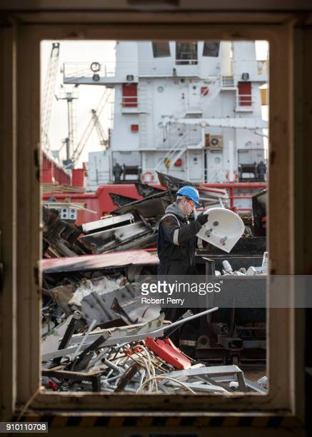 A worker carries an old sink for sorting on the decommissioned ship Lismore in Leith's Imperial Dry Dock on January 25 2018 in Leith Scotland The...