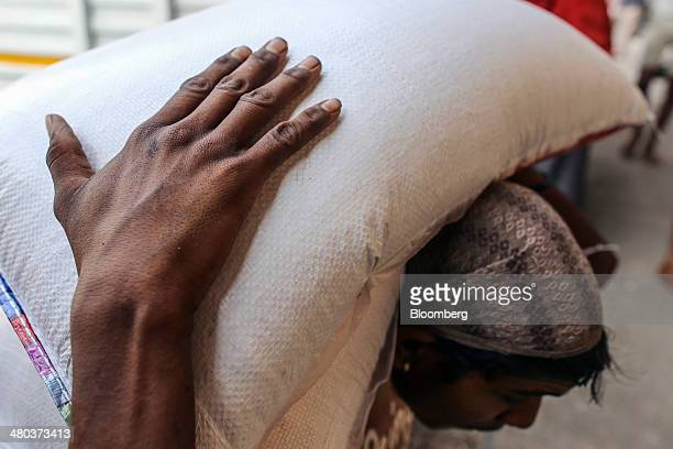 A worker carries bags of kolam rice at a warehouse in the Vashi Agricultural Produce Market Committee wholesale market in Mumbai India on Monday...