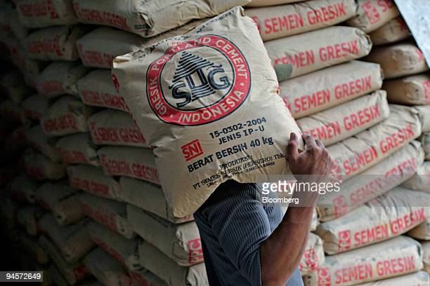 A worker carries bags of Semen Gresik cement at a shop in Jakarta Indonesia on Monday Nov 5 2007 PT Semen Gresik Southeast Asia's secondlargest...