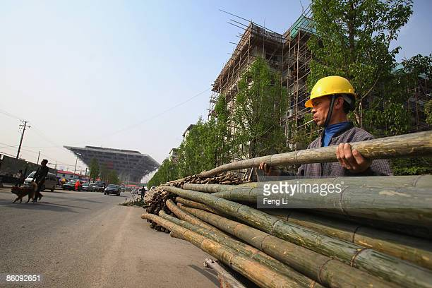 A worker carries bamboo for repairing peripheral residents' houses near the construction of the China Pavilion at the World Expo site on April 21...