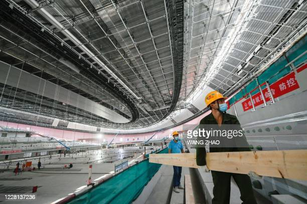 A worker carries building material inside the underconstruction National Speed Skating Oval the venue for speed skating events at the Beijing 2022...