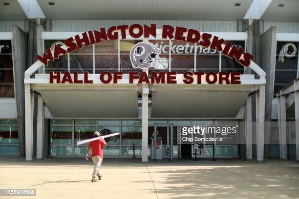 A worker carries building materials into the Hall of Fame Store at FedEx Field home of the NFL's Washington Redskins team July 13 2020 in Landover...