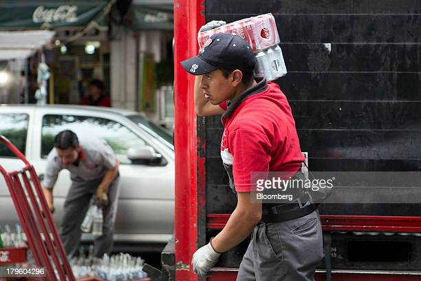 A worker carries cans of Cocacola while making a delivery in Mexico City Mexico on Thursday Sept 5 2013 CocaCola Femsa SAB a bottler and distributor...