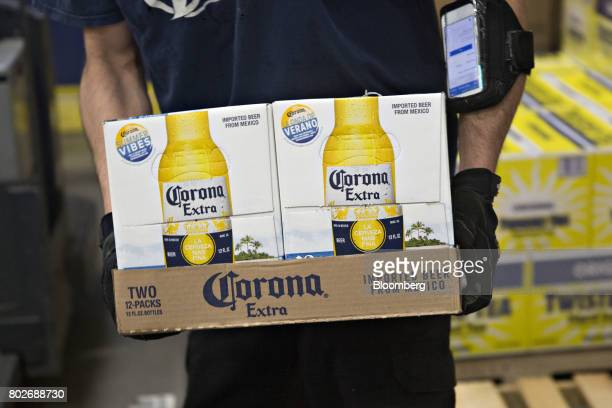 A worker carries cases of Constellation Brands Inc Corona beer at the Euclid Beverage LLC warehouse in Peru Illinois US on Tuesday June 27 2017...