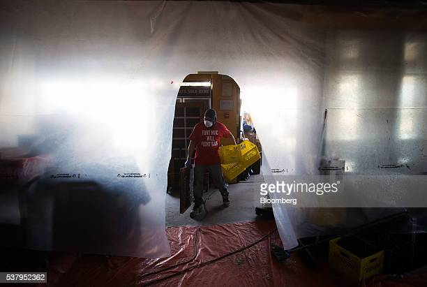 A worker carries crates in a brewery restaurant that was damanaged by wildfire in Fort McMurray Alberta Canada on Friday June 3 2016 Residents began...