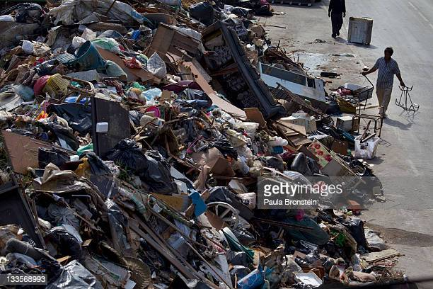 A worker carries debris to a makeshift garbage dump during a massive clean up in a neighborhood where flood waters have receded November 20 2011 in...