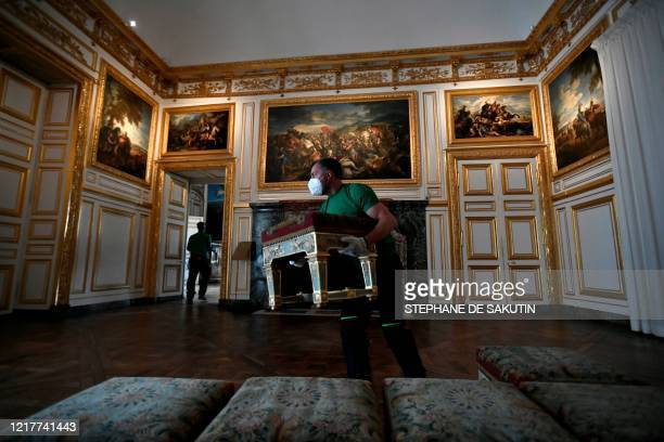 Worker carries furniture in a room of the Chateau de Versailles in Versailles near Paris, on June 5, 2020 on the eve of it re-opening after 82 days...