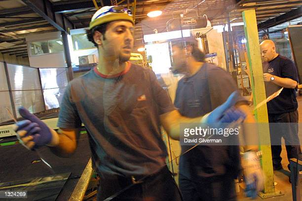A worker carries justcut bulletproof glass in the Oran Palmach factory in Kibbutz Zova July 10 2001 in central Israel Oran Palmach which began as a...