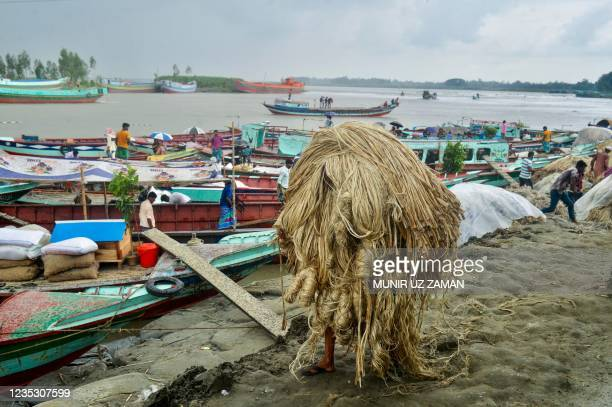 Worker carries jute to load on a boat at a rural market in Munshigonj on September 17, 2021.