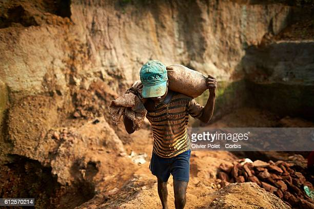 Worker carries out a bagful of excess earth out of the concession pool 28 March 2013 towards the end of the rain season near an Angolan village not...