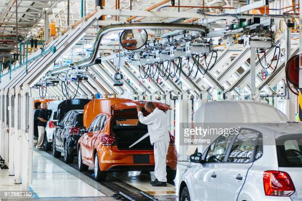 A worker carries out a quality control inspection inside the boot area of a VW Polo automobile on the production line at the Volkswagen AG plant in...