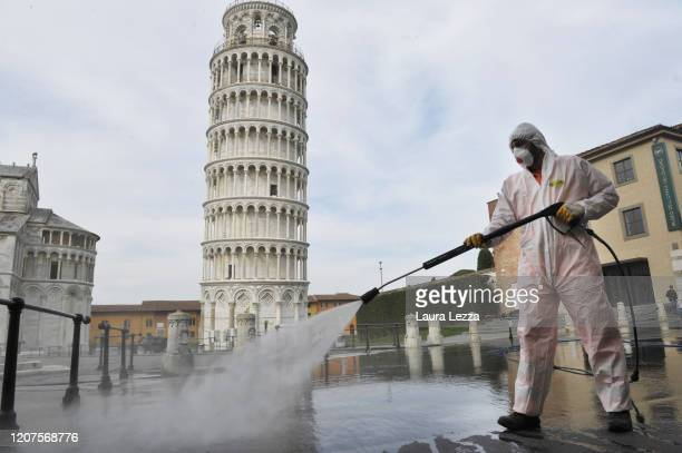 Worker carries out sanitation operations for the Coronavirus emergency in Piazza dei Miracoli near to the Tower of Pisa in a deserted town on March...