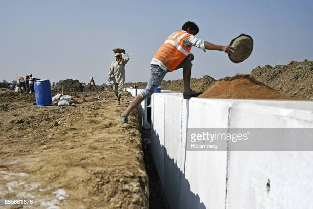 A worker carries sand in a container on his head at an under construction sewerage system on the project site for a 920squarekilometer industrial...