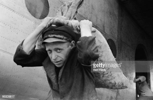Worker carries supplies from a British aircraft during the Berlin Airlift, 18th September 1948. Original publication: Picture Post - 4643 - The...