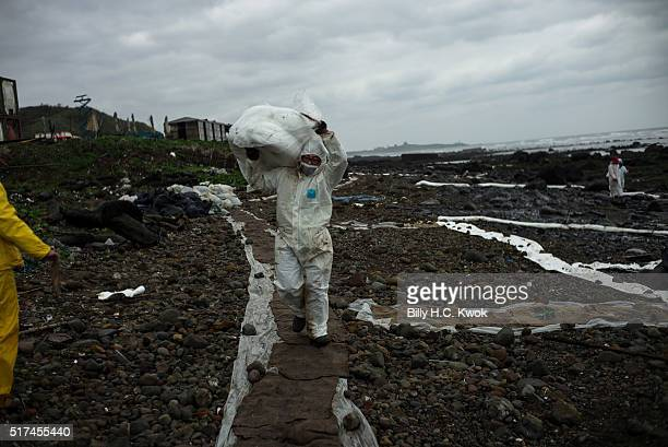 Worker carry contaminated materials at a coastal area affected by an oil spill near Taiwan's north coast on March 25, 2016 in Shihmen, Taiwan. An oil...