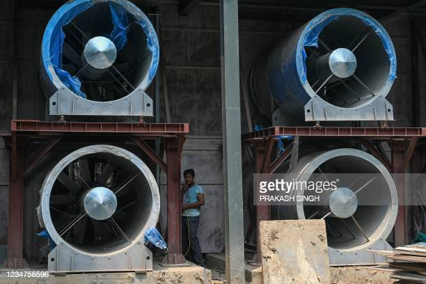 Worker carry on works next to large fans at the construction site of a 25-metre high smog tower near Connaught Place in New Delhi in New Delhi on...