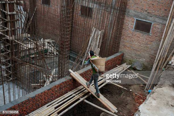 A worker carrying a basket of cement on his back walks up a ramp to a residential building under construction in Kathmandu Nepal on Wednesday Nov 1...