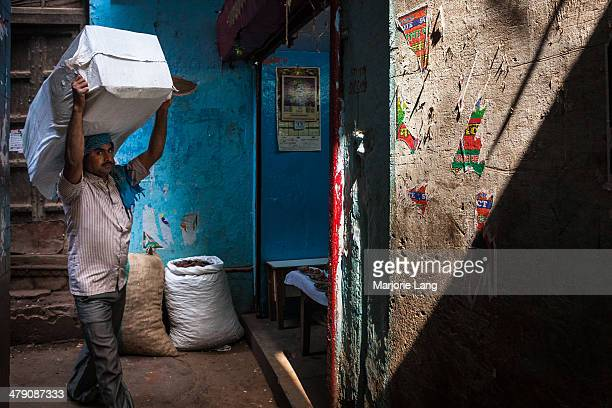 CONTENT] Worker carrying a heavy load in a narrow blue alleyway of the spices market area near Chandni chowk in old Delhi India