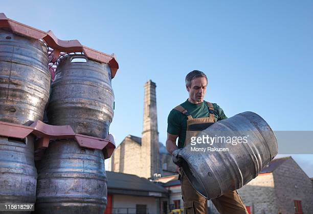 Worker carrying barrel outside brewery