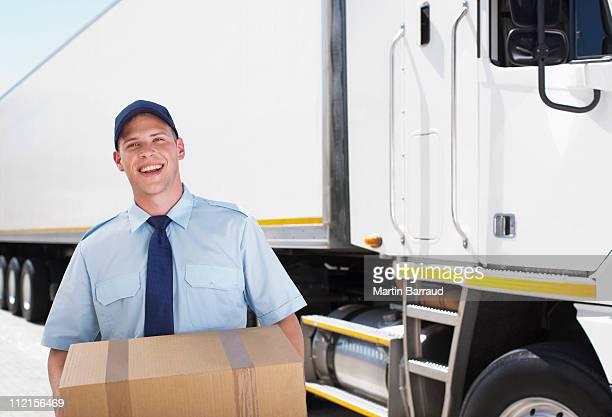 Travailleur transportant box près de semi-remorque