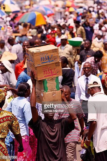 worker carrying boxes in nigerian market - lagos stock-fotos und bilder