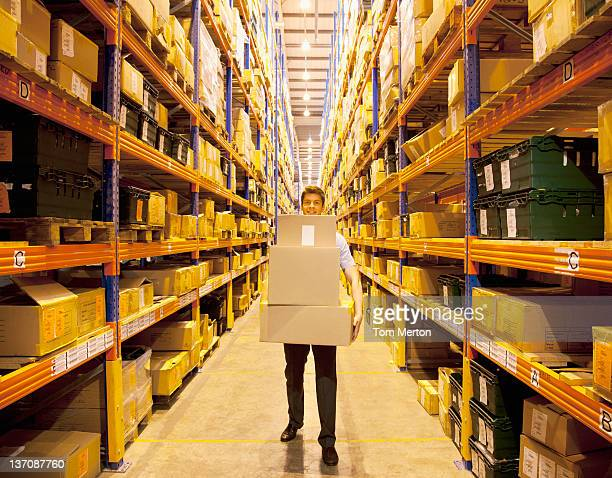 worker carrying boxes in warehouse - luggage hold stock pictures, royalty-free photos & images
