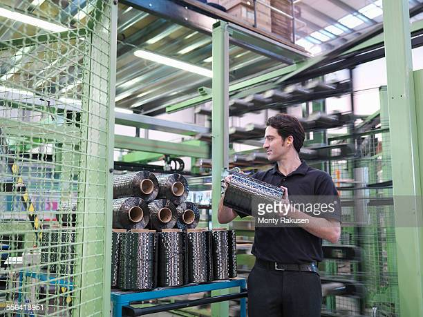 Worker carrying carbon fibre thread in carbon fibre factory