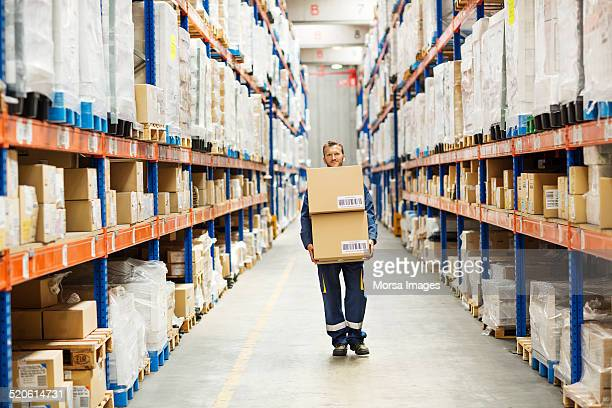 worker carrying cardboard boxes at warehouse aisle - carrying stock pictures, royalty-free photos & images