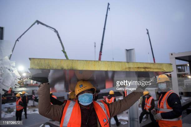 A worker carrying construction material at Huoshenshan hospital as new hospitals are built to tackle the coronavirus on January 28 2020 in Wuhan...
