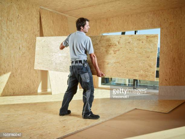 worker carrying flakeboard - carrying stock pictures, royalty-free photos & images