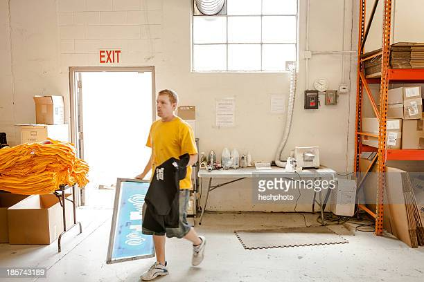 worker carrying frame and t-shirt in screen printing workshop - heshphoto - fotografias e filmes do acervo