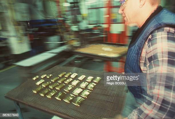 Worker carrying ingots taking them out of their moulds and putting on a grate