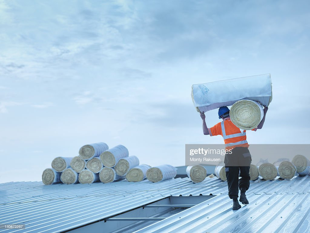 Worker carrying insulation on roof : Stock Photo