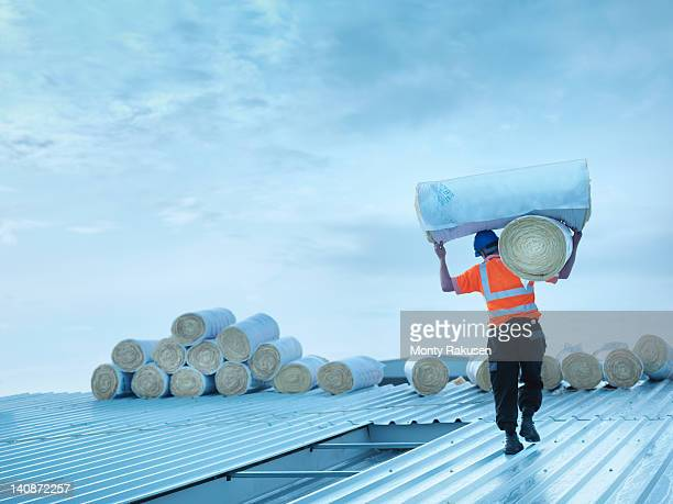 worker carrying insulation on roof - isoliert stock-fotos und bilder