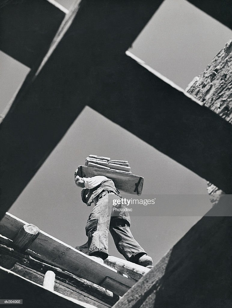 Worker carrying materials, seen from below : Stock Photo