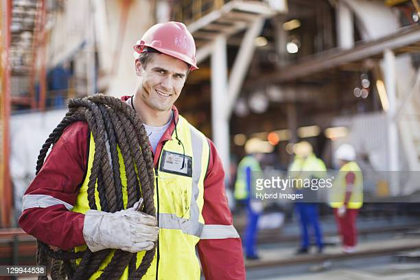 Worker carrying rope on oil rig