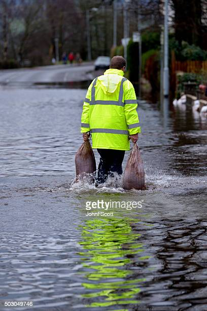 worker carrying sandbags through flood water - sandbag stock pictures, royalty-free photos & images